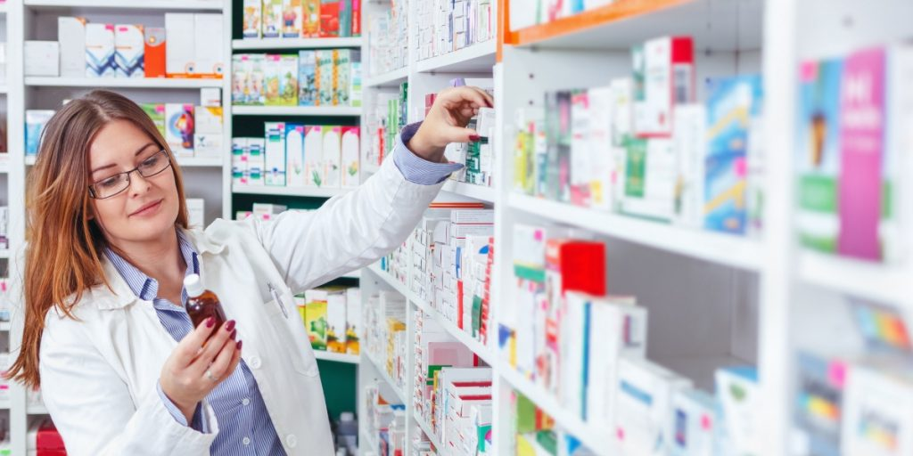 Pharmacist Looking at Medicine in Pharmacy