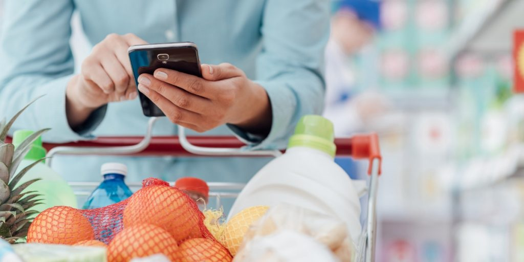 Woman on Cell Phone in Grocery Store Digital Coupons